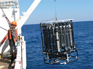 Researcers deploy a water sampling device to measure conductivity, temperature and depth (CTD) at different points of the water column. Photo credit: Alan Shiller USM
