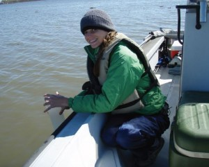 A researcher collects a water sample to assess water quality in Breton Sound, LA.