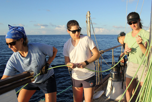 "On the Ocean Alliance's R/V Odyssey, a team of ""super-tough women"" help Kait Frasier (in background) deploy a hydrophone array. Using these underwater microphones, they listen for animal sounds and match them with the species that makes them. Doing this at sea allows them to find dolphins they hear and determine their type. (Photo provided by Frasier)"
