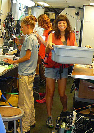 Alex Harper transports bottles of collected seawater samples across a crowded laboratory on the R/V Weatherbird II. The science crew included researchers from University of South Florida, Fish and Wildlife Conservation Commission, the USGS and the University of Delaware. (Photo credit: Natalie Geyers)
