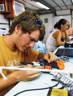 Nathan solders customized expanded battery packs into SPOT GPS units aboard R/V F.G. Walton Smith to compensate for the extended transmission time required by the GLAD experiment. (Photo credit: Tamay Özgökmen)
