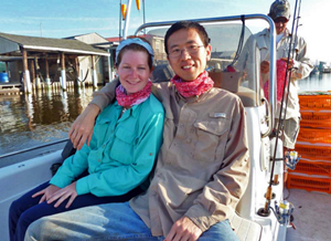 Xuan (right) and Brooke Hesson (left) en route to the marshes to collect insects and take soil samples. The boat's captain, Jay Winters, can be seen in the background. (Photo provided by Xuan Chen)