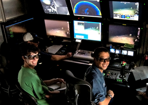 ROV pilot Toshi Mikagawa (center), and Samantha Berlet (right) wear 3D glasses to view live footage of coral beds deep beneath the Gulf. (Photo provided by Rich Dannenberg)
