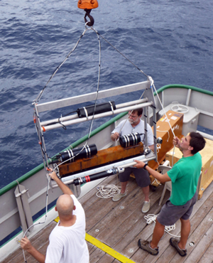 Conor (far right), Mark Graham (right), and Texas A&M – Corpus Christi environmental scientist Derek Bogucki (left) lower an optical turbulence sensor overboard to sample micro variations in temperature near the ocean surface. (Photo credit: David Nadeau)