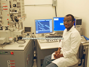 Sehinde, at the Tulane University Coordinated Instrumentation Facility, sits beside the scanning electron microscope he uses to image halloysite nanotubes and oil droplets stabilized by them. (Photo by Chike Ezeh)