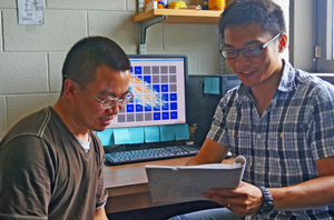 Bicheng (right) discusses his research with a colleague. A new technique that he is using to track oil plumes is visible on the monitor behind them. (Provided by Bicheng Chen)