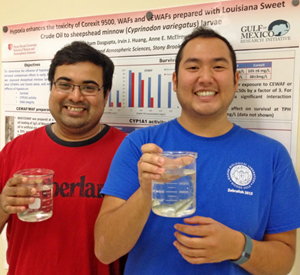 Subham Dasgupta (left) and Irvin Huang (right) gave a poster presentation about their research at the 2015 Gulf of Mexico Oil Spill & Ecosystem Science conference. Here, they are holding beakers with early life stage fish similar to those used in their study. (Photo provided by Anne E. McElroy)