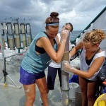 Eckerd College students transferring a multicore from a collection barrel to a working barrel aboard the R/V Weatherbird II, June 2011. (Photo provided by Gregg Brooks)