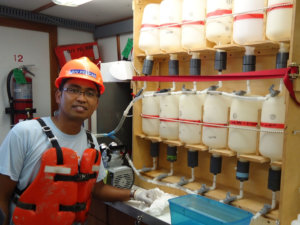 Dr. Hernando Bacosa works at the seawater filtration system aboard the R/V Pelican 2013 cruise to the Deepwater Horizon site in the Gulf of Mexico. Photo provided by Hernando Bacosa.