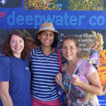 Graduate student Fanny Girard (left) joins game-day fans at the ECOGIG-II Ocean Discovery Zone. The coral banner makes a beautiful photo backdrop! (Photo by ECOGIG-II)