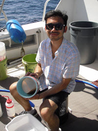 Co-author (and former NOAA NGI Diversity Program intern) Jeff Fang rinses a plankton sample at sea. (credit: USM Fisheries Oceanography and Ecology Lab)