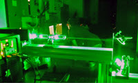 The laser set up in operation as former postdoc David Murphy and fellow Ph.D. student Kaushik Sampath monitor the results in the background. (Provided by Xinzhi Xue)