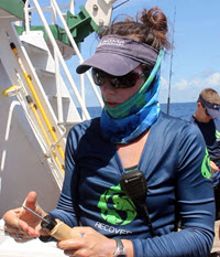 PhD student Lela Schlenker holds a device used to outfit captured mahi with data-collecting tags. (Provided by RECOVER)