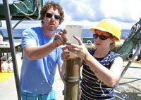 Melissa and Travis Washburn slice a sediment core for analysis. (Photo by Ben Prueitt)